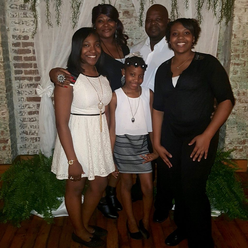 Ebony, her mom and dad, her little sister and her big sister, all pose for a family photo.