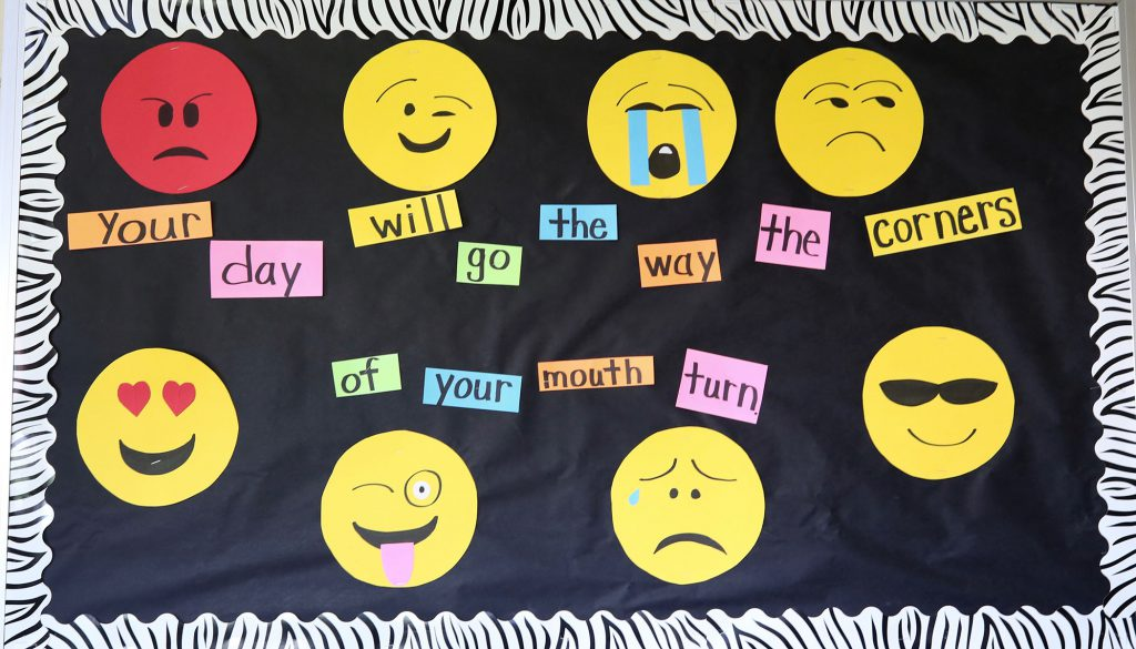 """QUE bulletin board which says, """"Your day will go the way the corners of your mouth turn."""