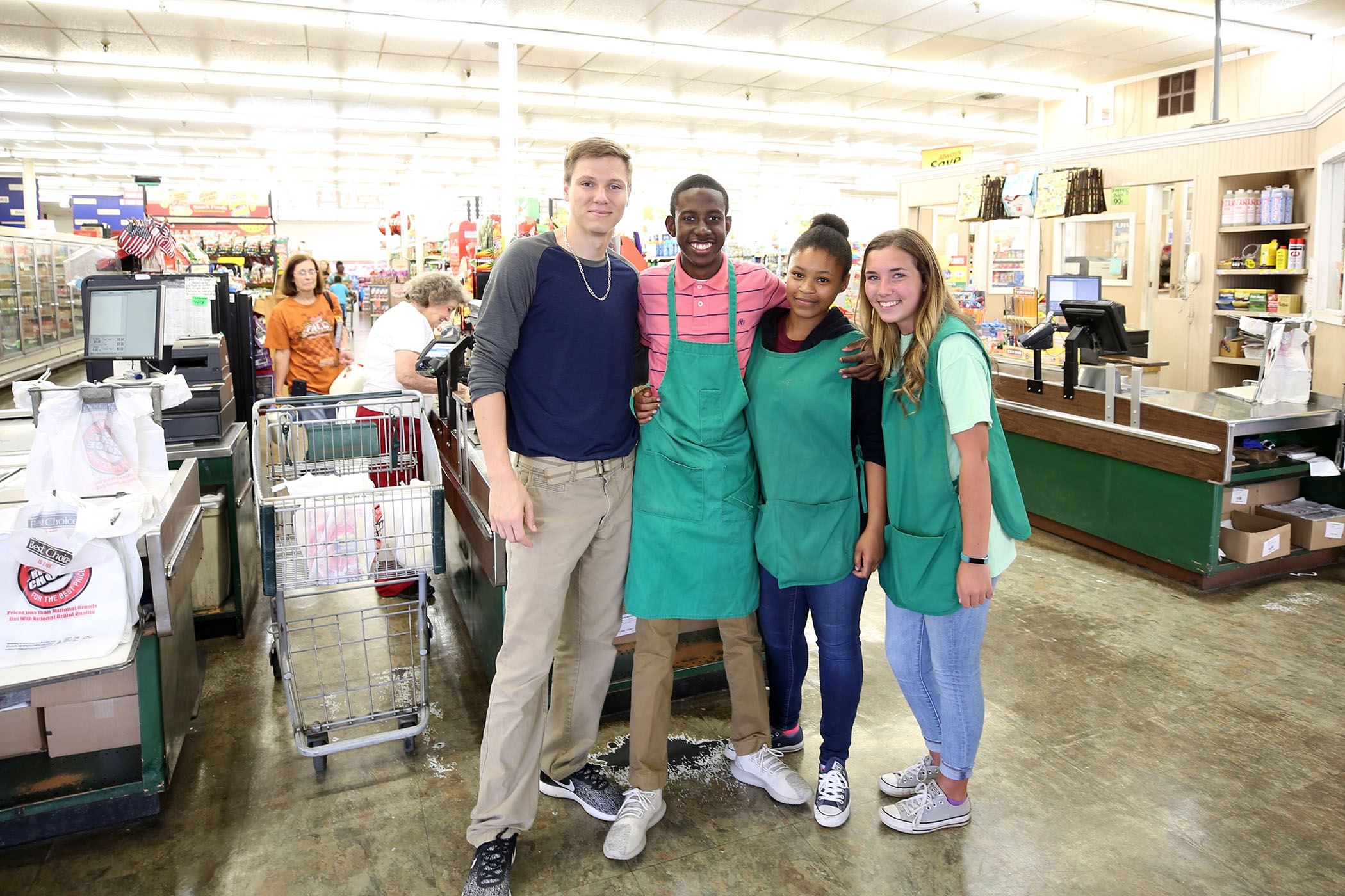 Tyshun stands with his coworkers/classmates at the local grocery store where he works after school.