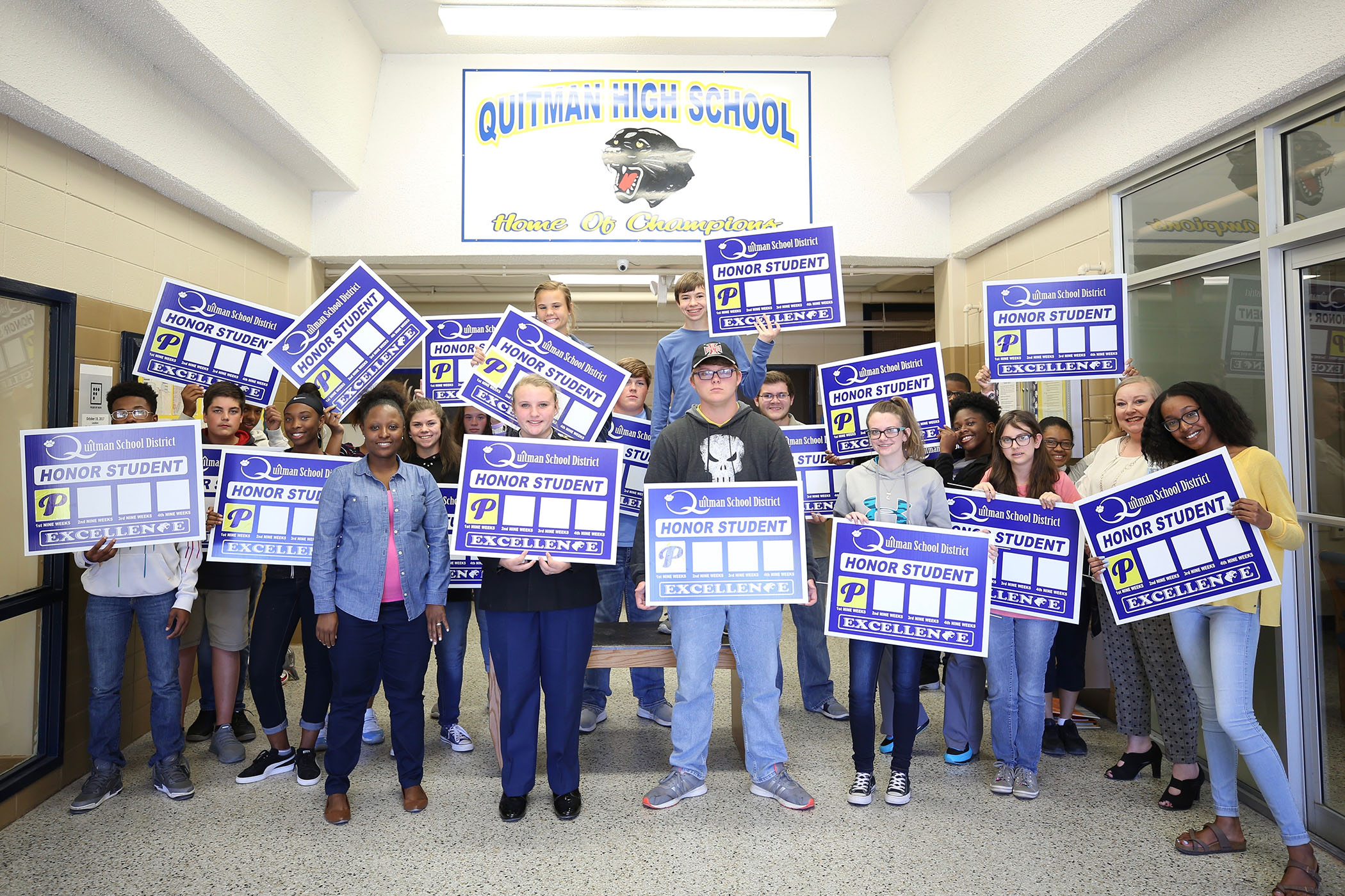 QHS freshmen stand with their honors yard signs.