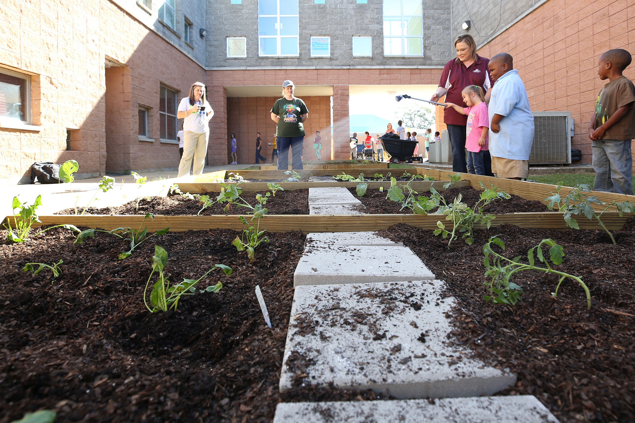 QLE students water their garden.