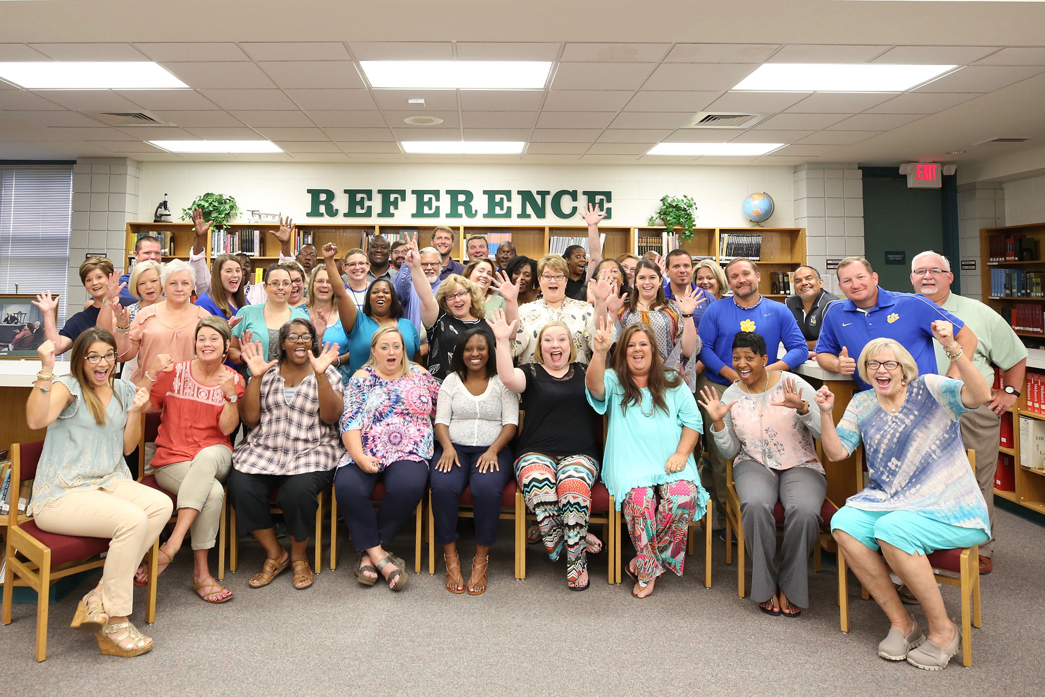 QHS faculty pose in school's library.