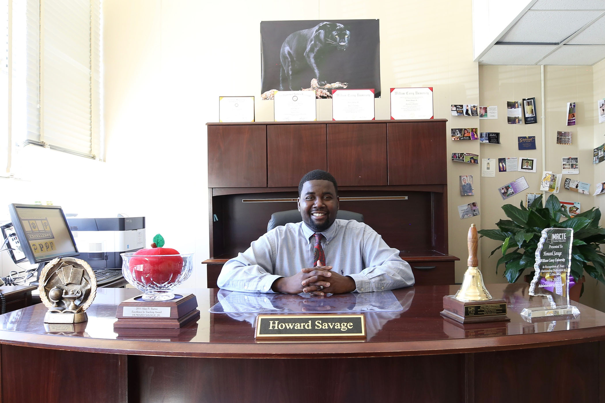 Dr. Howard Savage sits at his desk in the QHS Principal office.