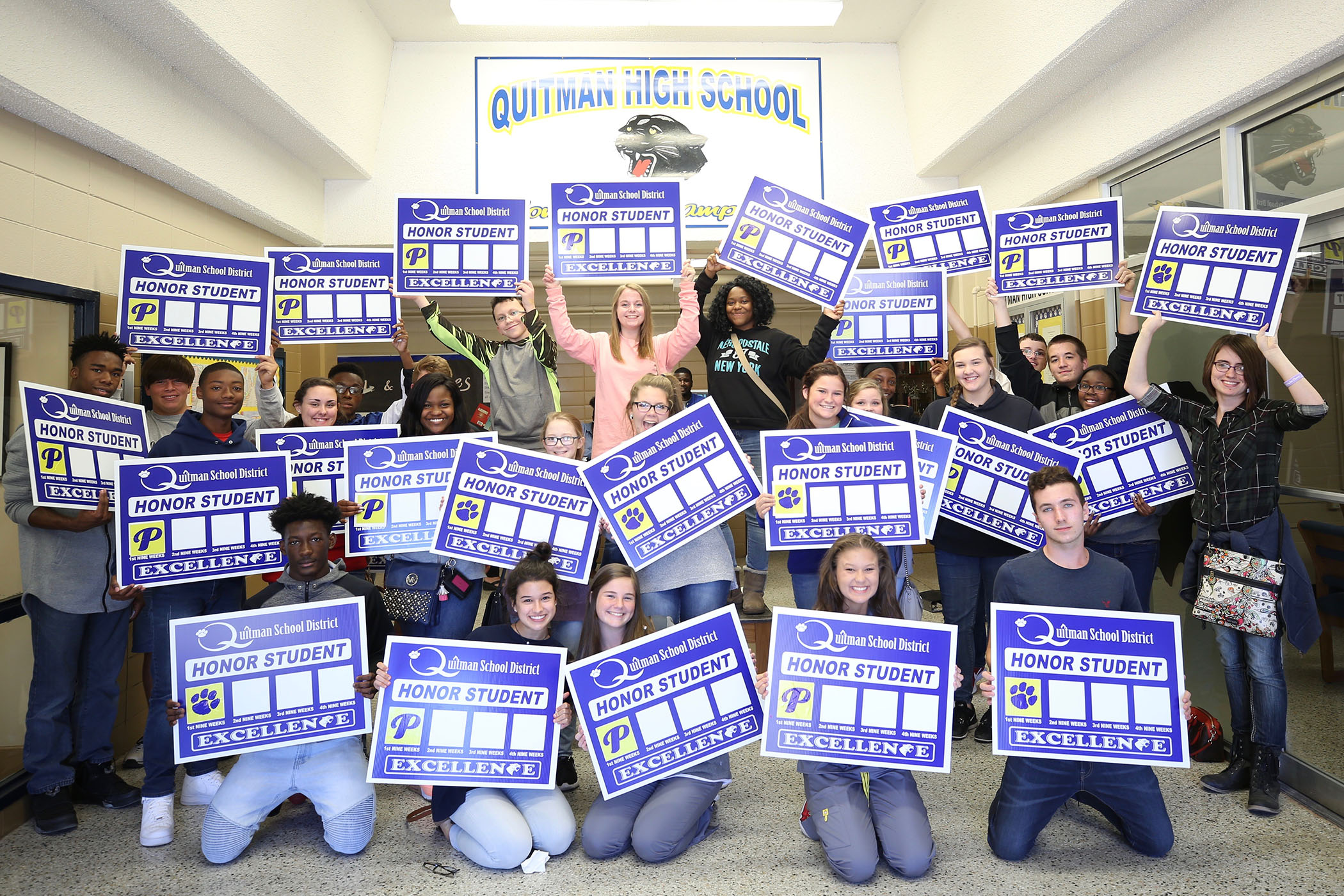 QHS sophomores stand with their honors yard signs.
