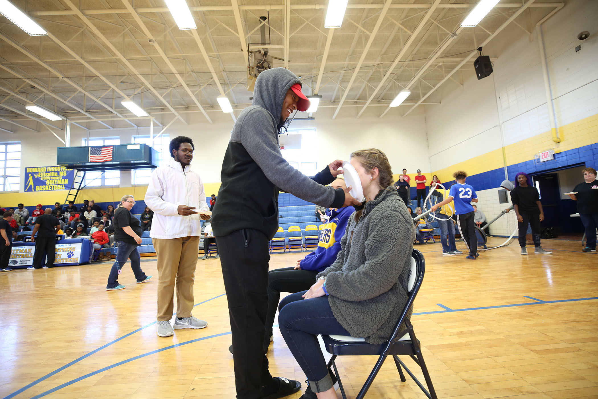 A QHS senior delivers a pie in the face of a freshman.