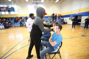 A QHS senior puts pie in the face of a sophomore.