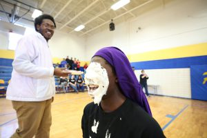 A QHS junior's face covered in pie.