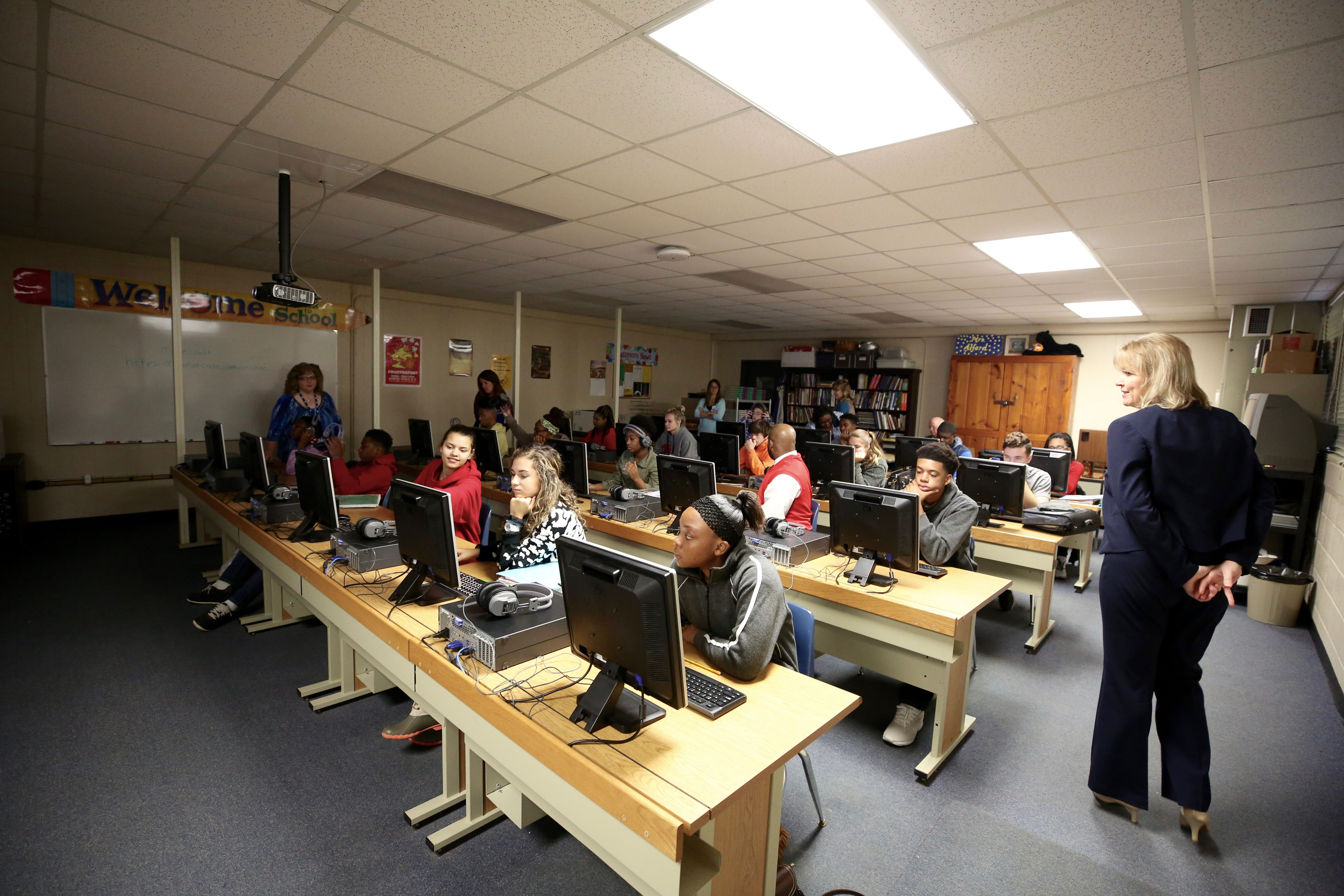 QHS students sit in a classroom and do an Hour of Code with the help of Mississippi State University computer science personnel.