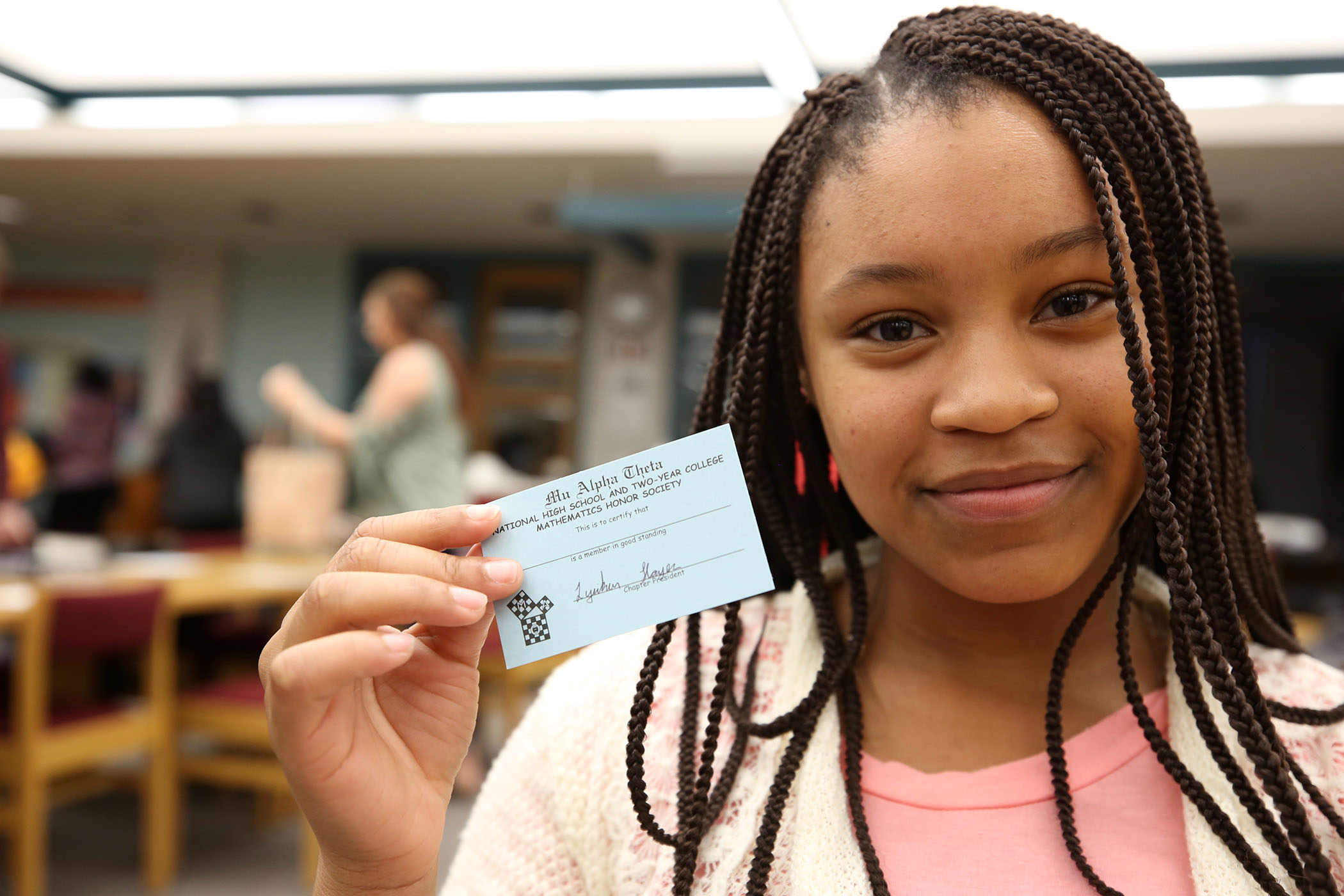 Mu Alpha Theta member holds up her 2017-2018 membership card.