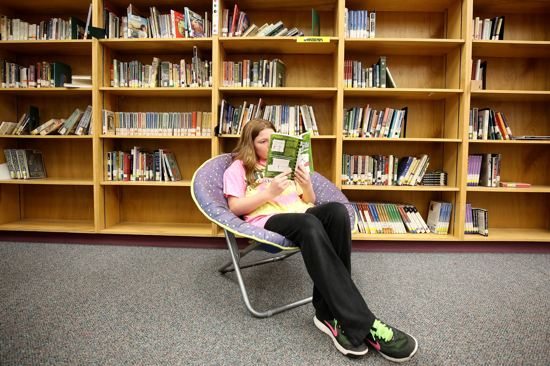 A QJH student poses with a book in the school's library.