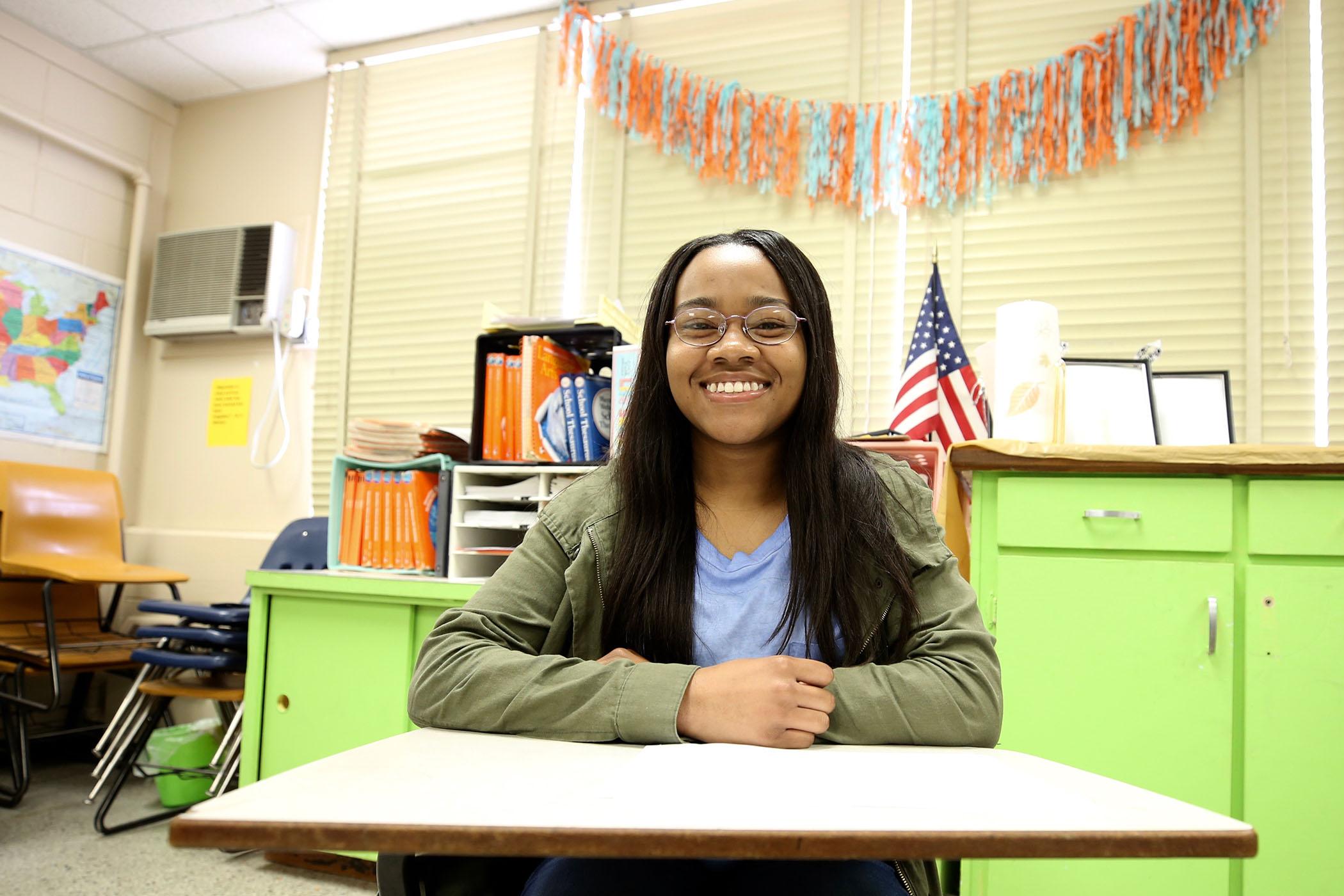 Amiya sits in a classroom.