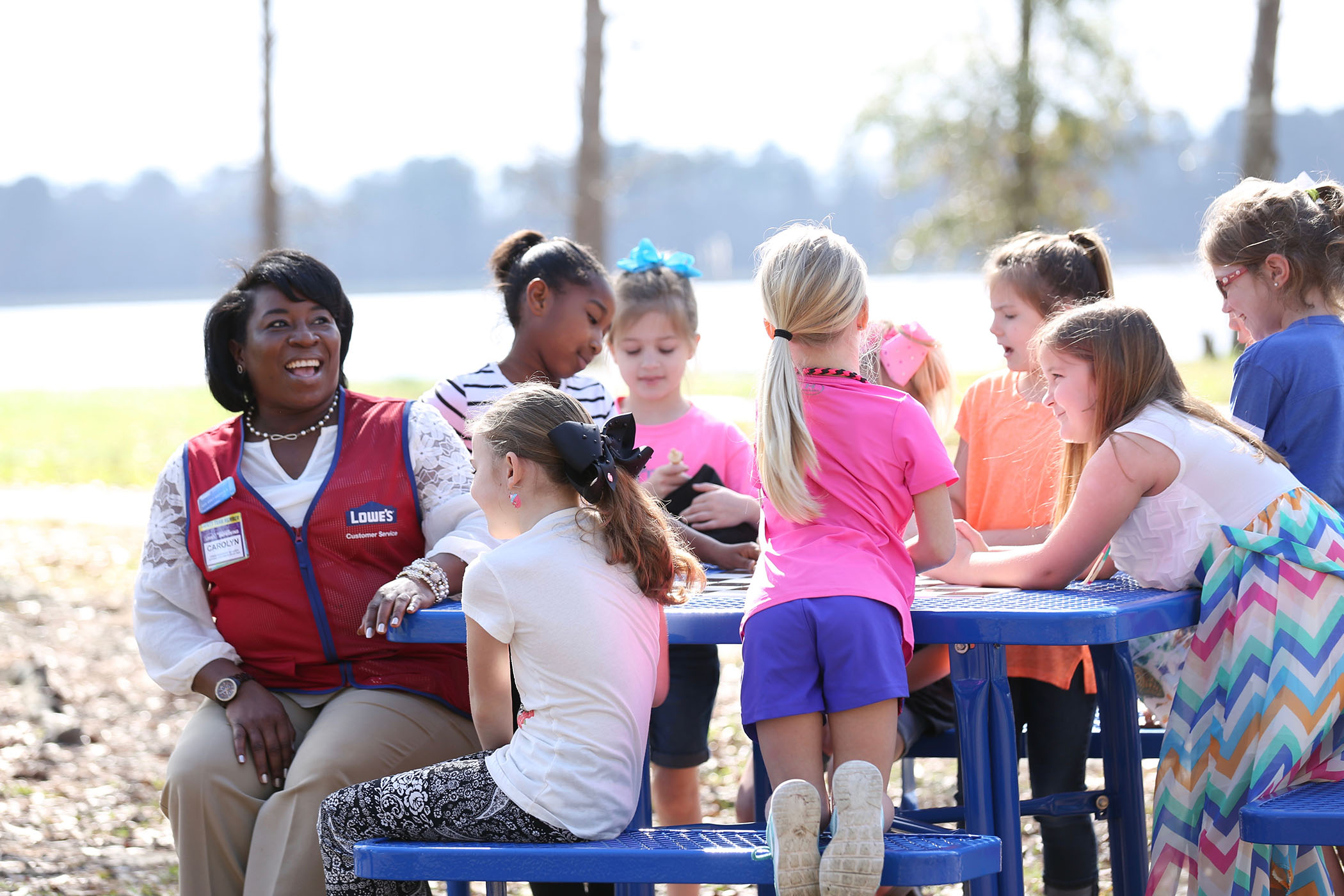 A Lowe's employee sits with SWAT students as they prepare to play chess.