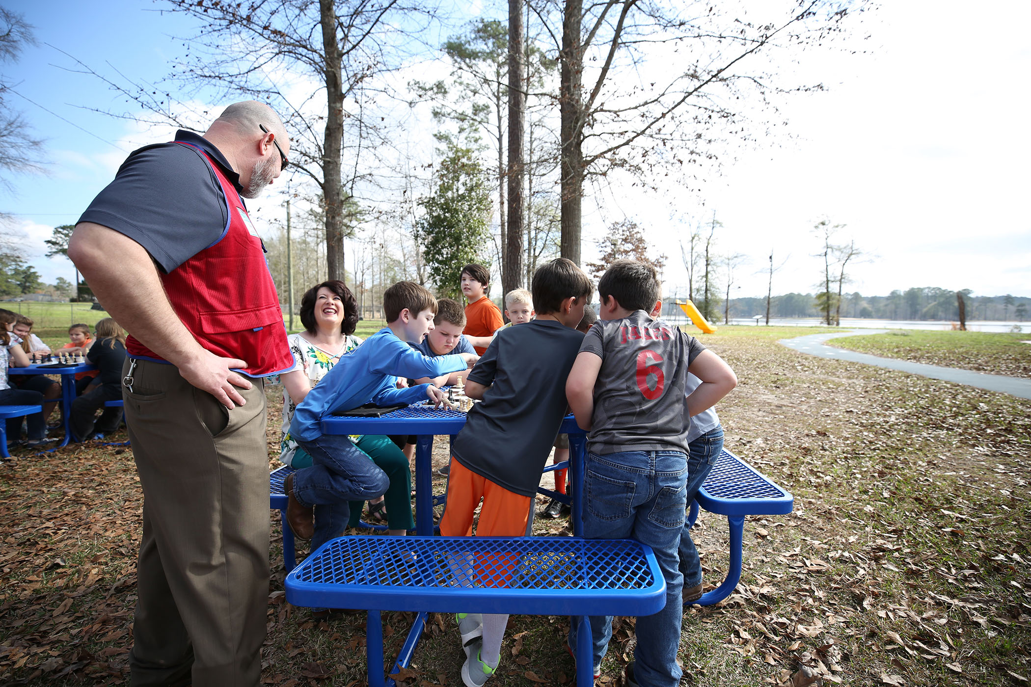 A Lowe's employee looks on as SWAT students play a game of chess.