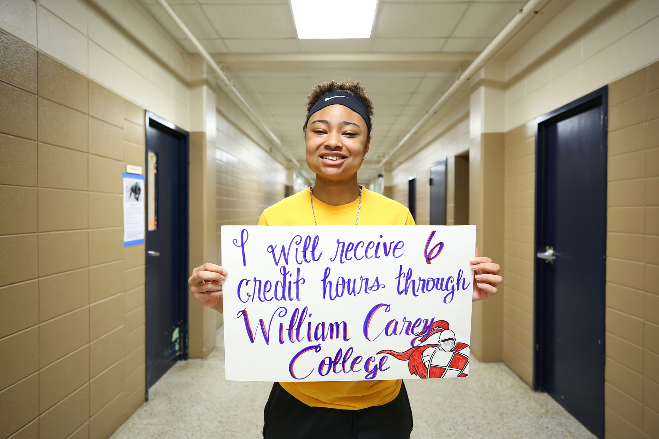 Reagan stands with a sign declaring that she will graduate with 6 college credit hours.