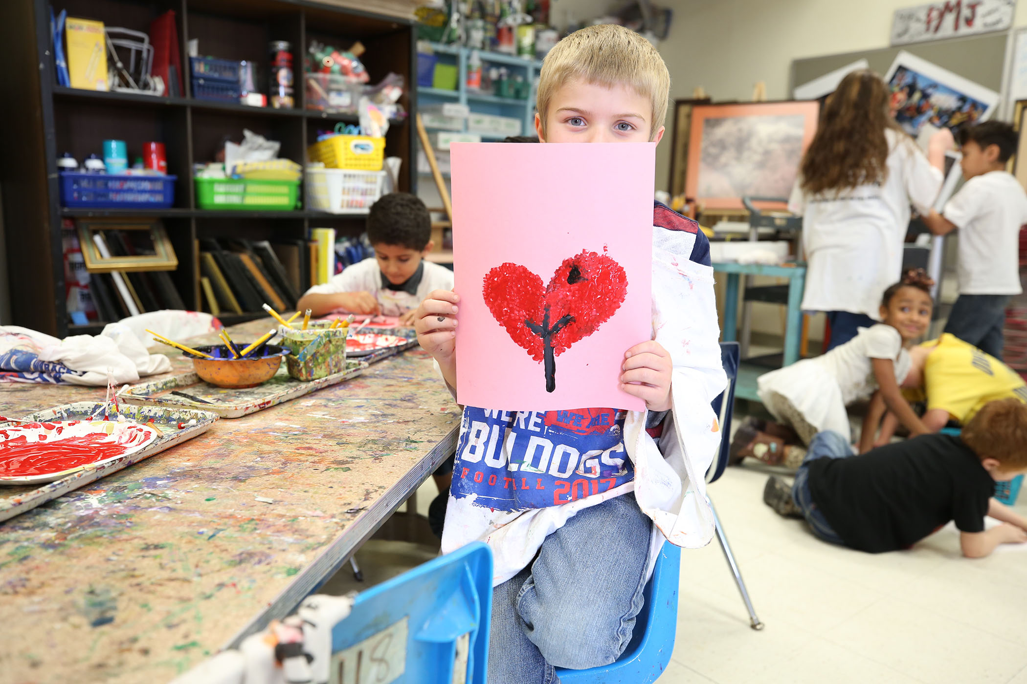 A QLE student holds up his artwork.