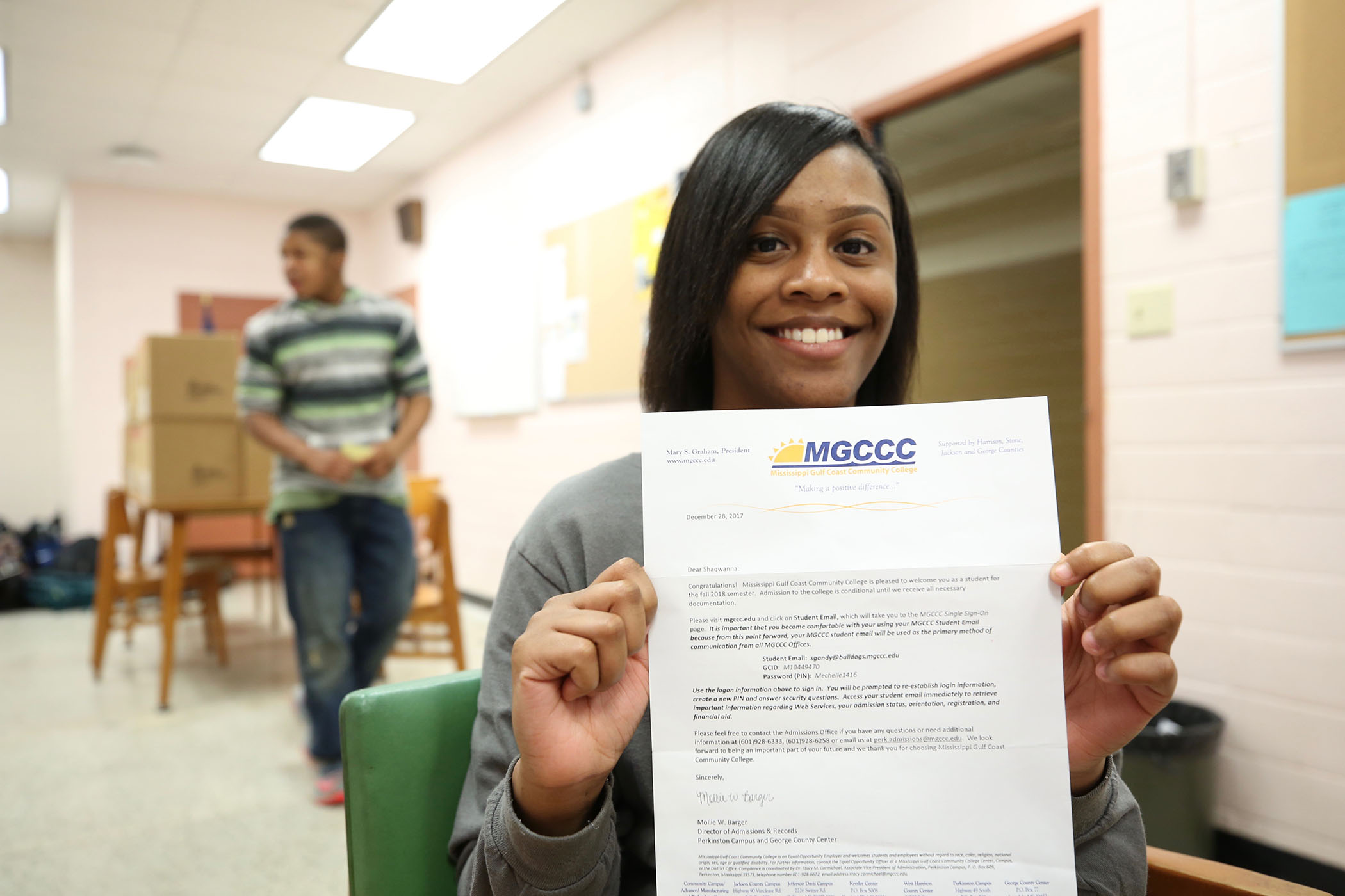 A QHS senior holds up her acceptance letter to MGCCC.