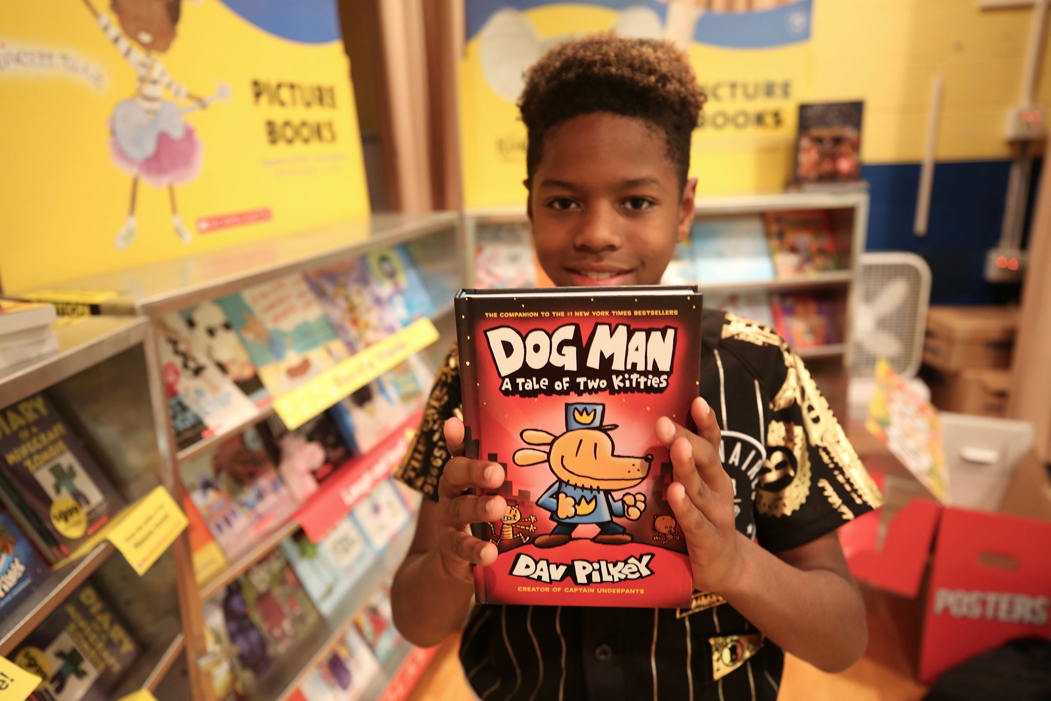 A QUE student holds up his favorite book series at the school's book fair.