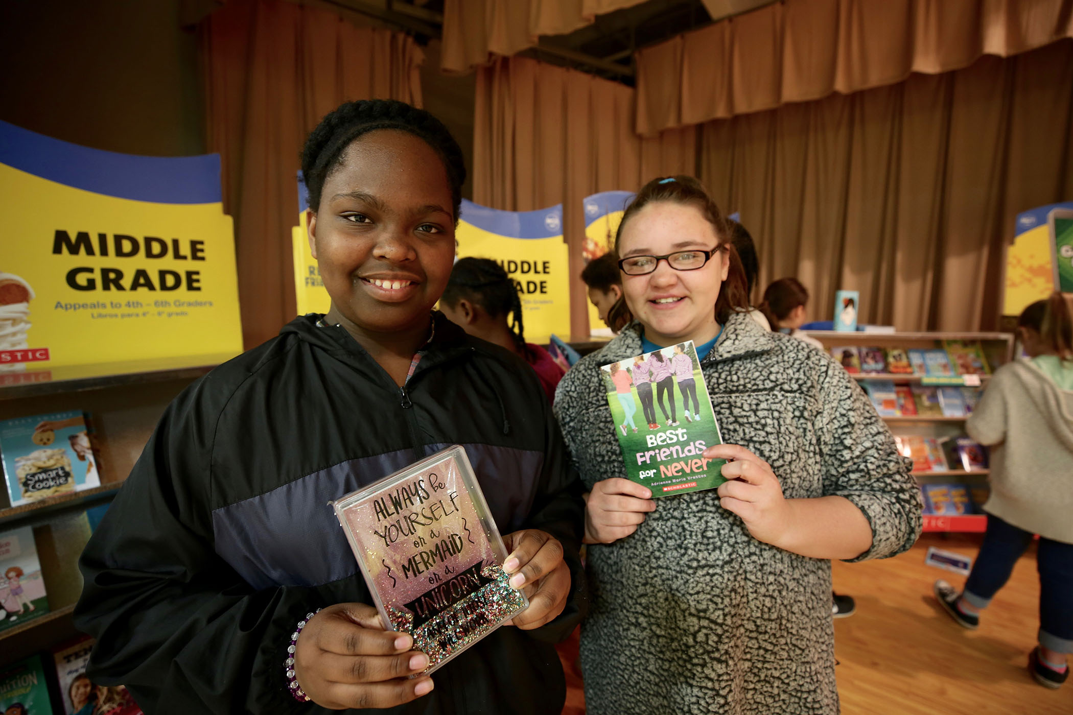 QUE students hold up their favorite books at the school's book fair.