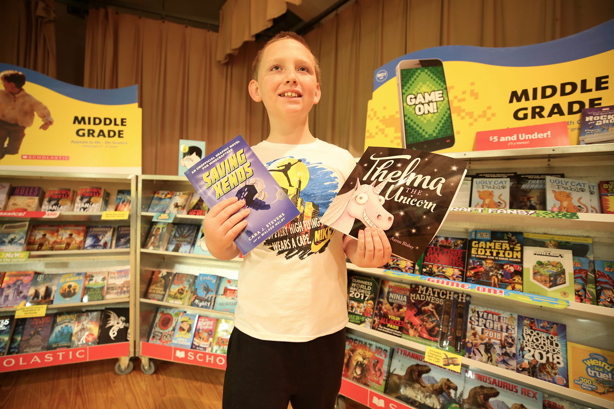 A QUE student holds up his favorite book at the school's book fair.