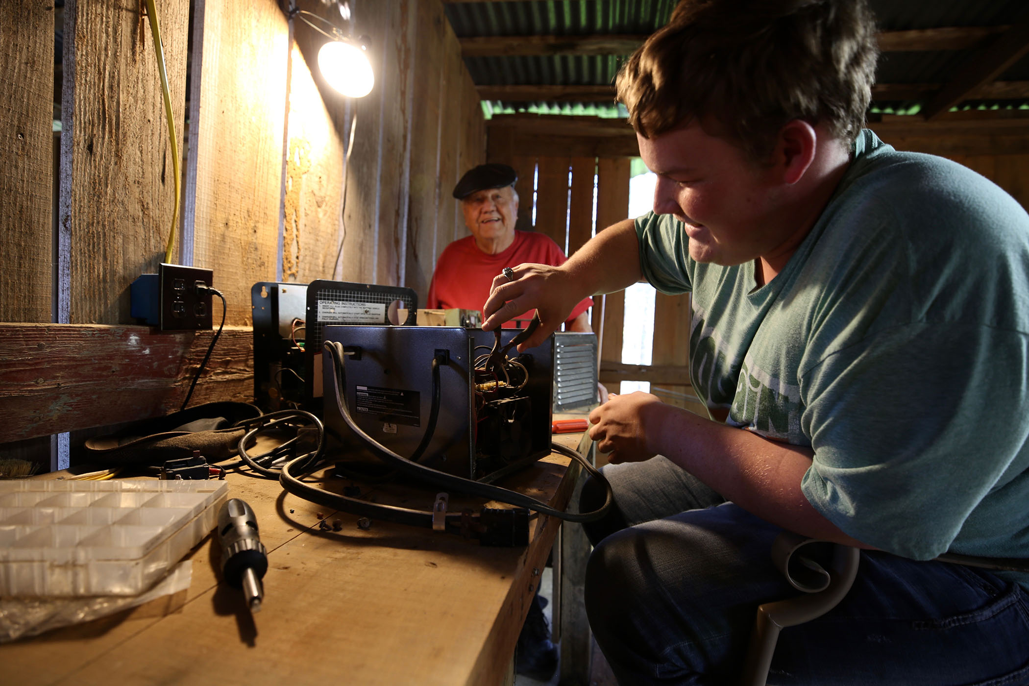 Scottie works on a battery in his and papaw's shop.