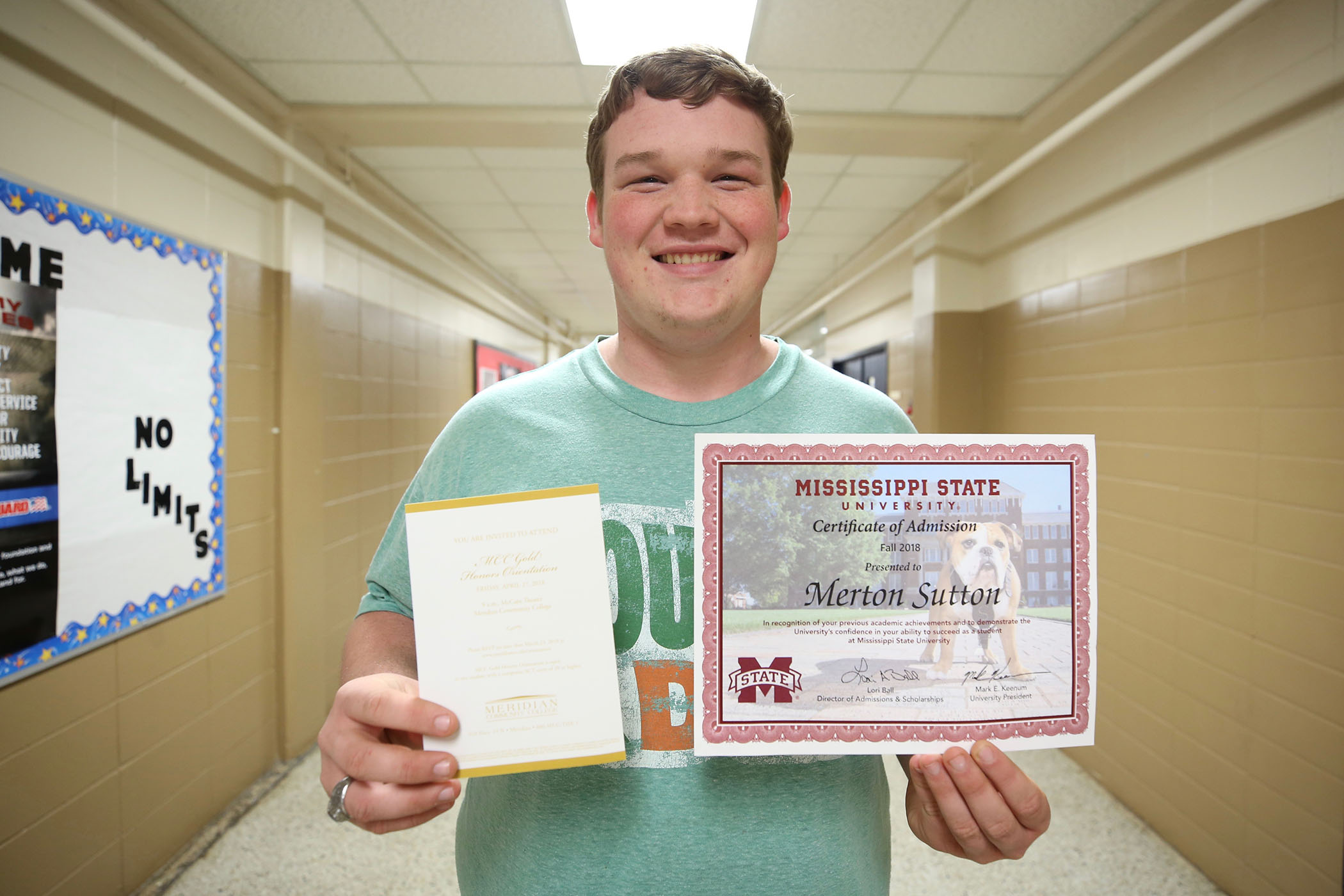 Scottie holds up his acceptance letters to Meridian Community College and Mississippi State University.