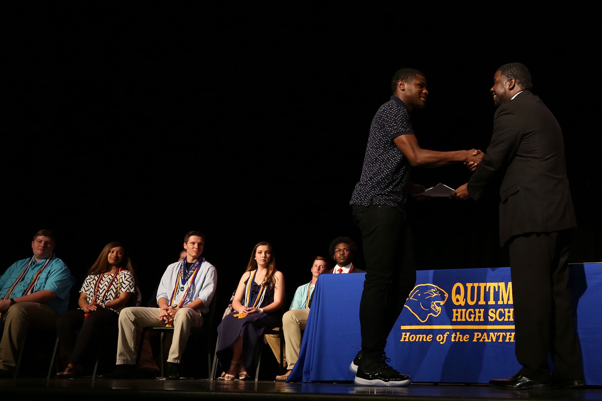 QHS senior accepts an award from Dr. Savage.