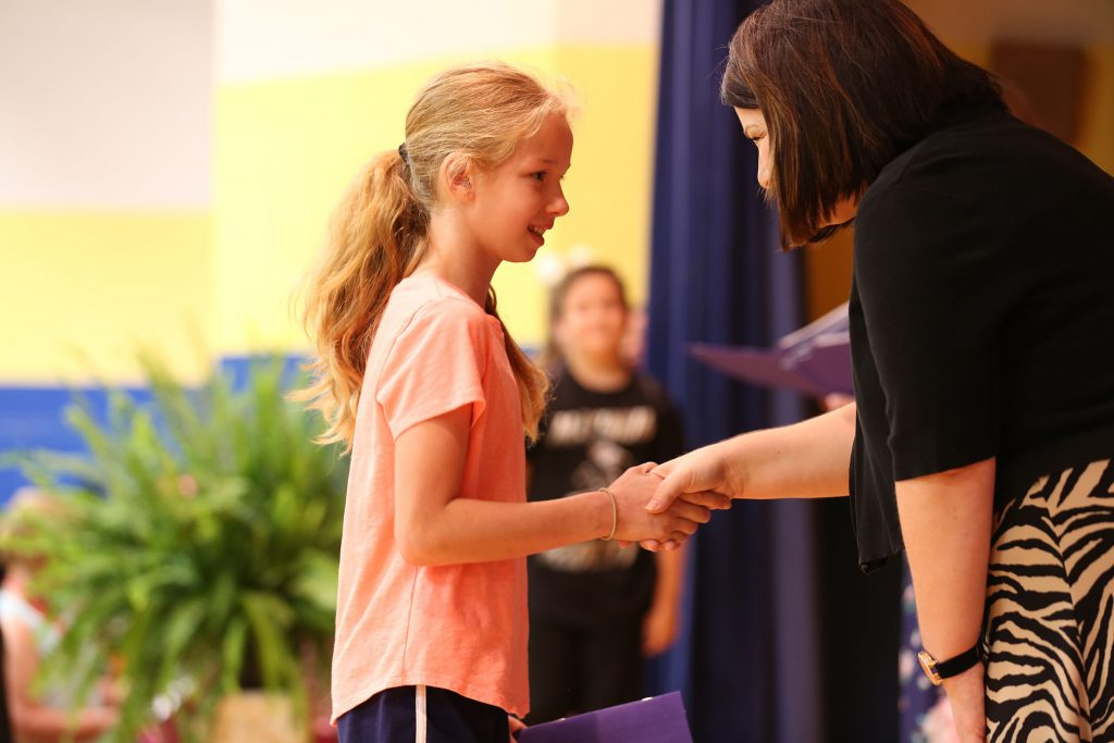 A QUE student accepts an award from Mrs. Ivey.