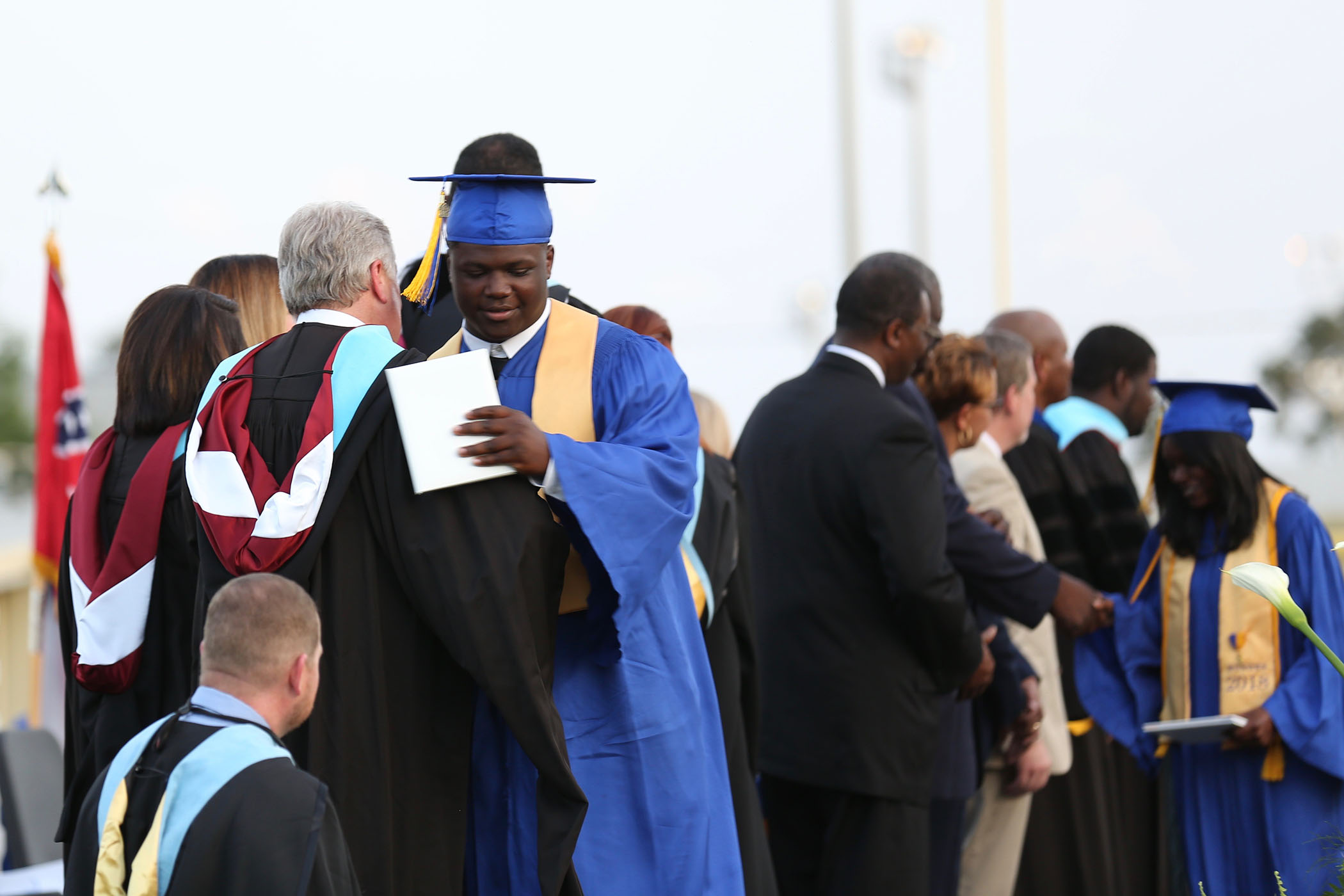 2018 Graduate hugs Coach Russell.