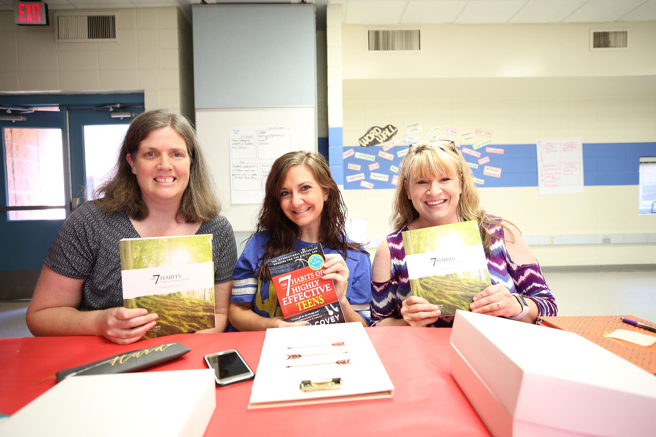 QSD teachers hold up Stephen R. Covey books.