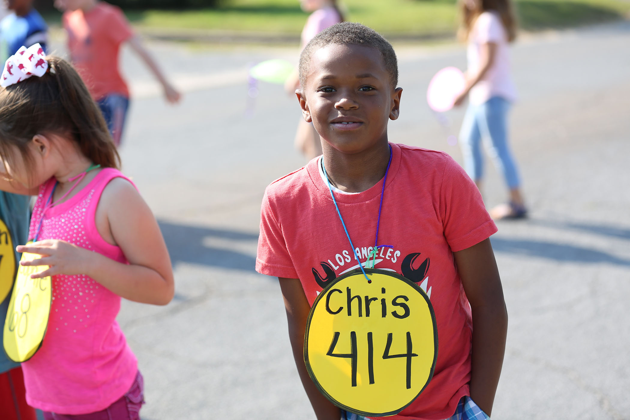 A QLE student wears a sign announcing that he read 414 books this year.