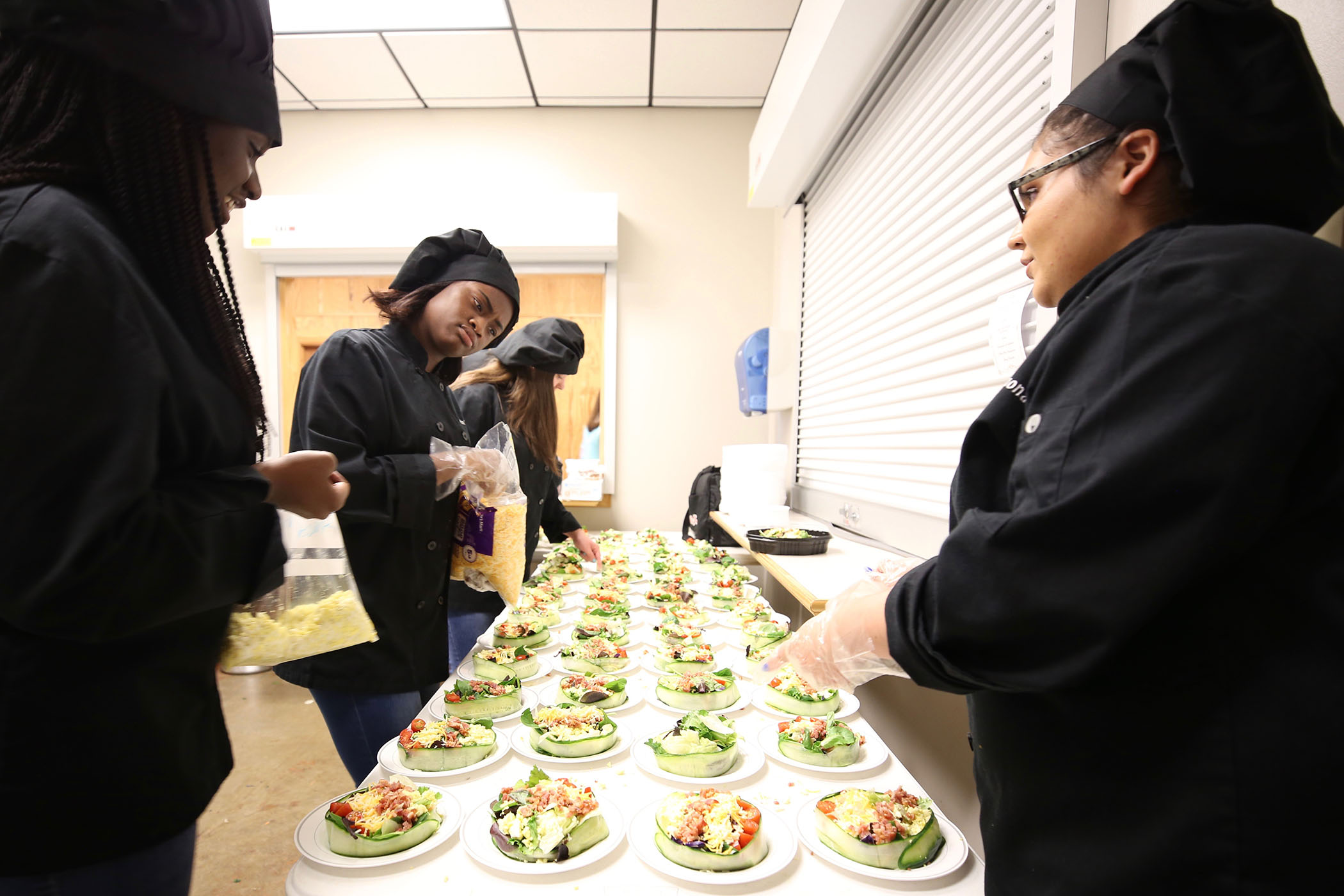 Culinary arts class is preparing the salads for the CTE Completion Ceremony.