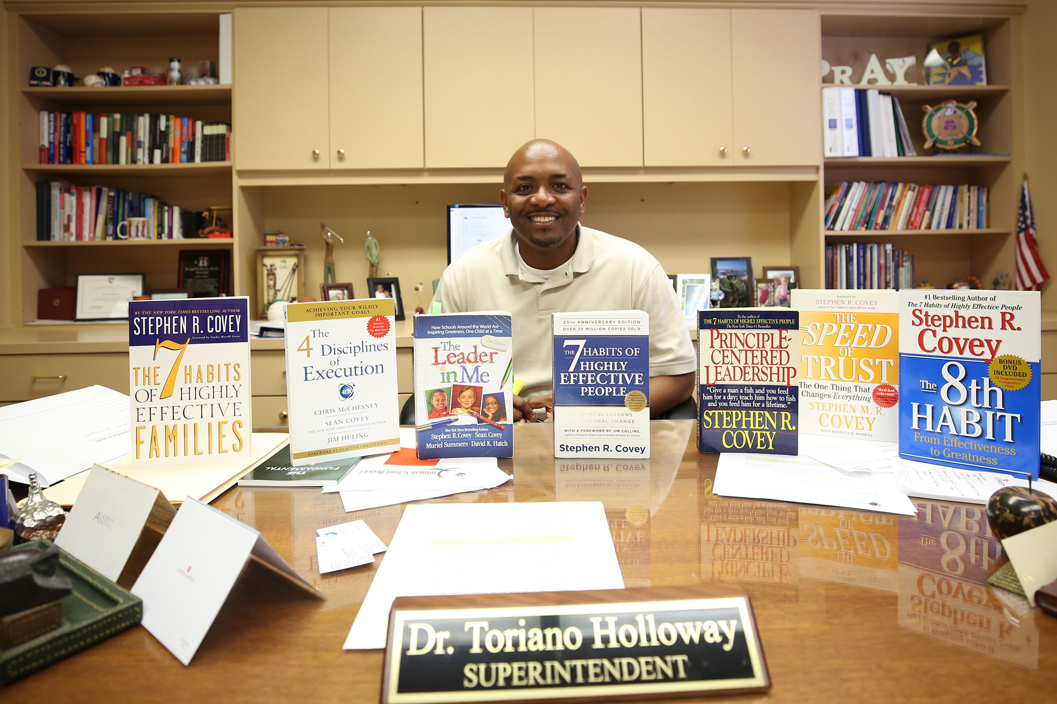 Dr. Holloway sits at his desk with books by Stephen R. Covey.