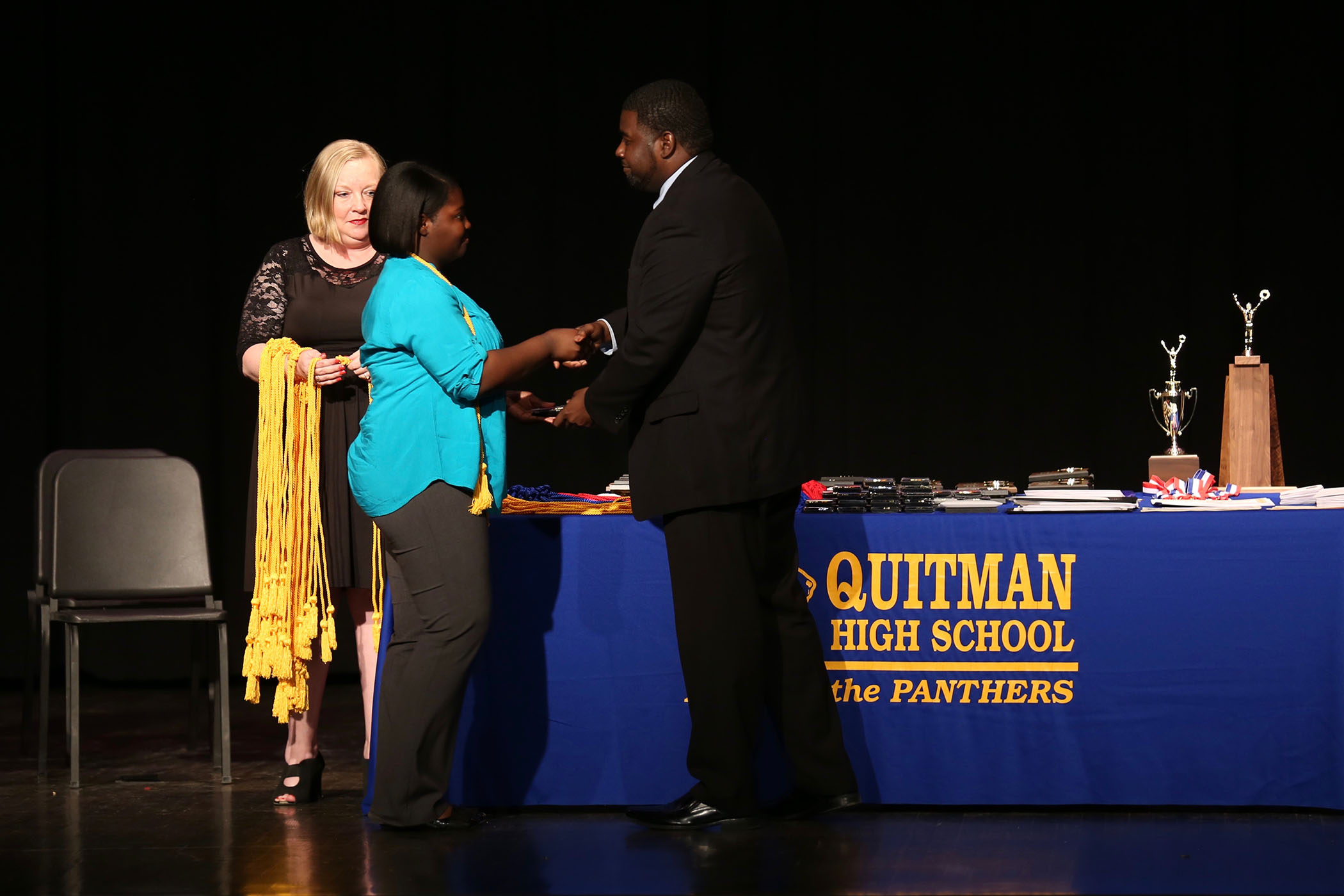 Dr. Savage present a QHS senior with an award on QHS Awards Night.