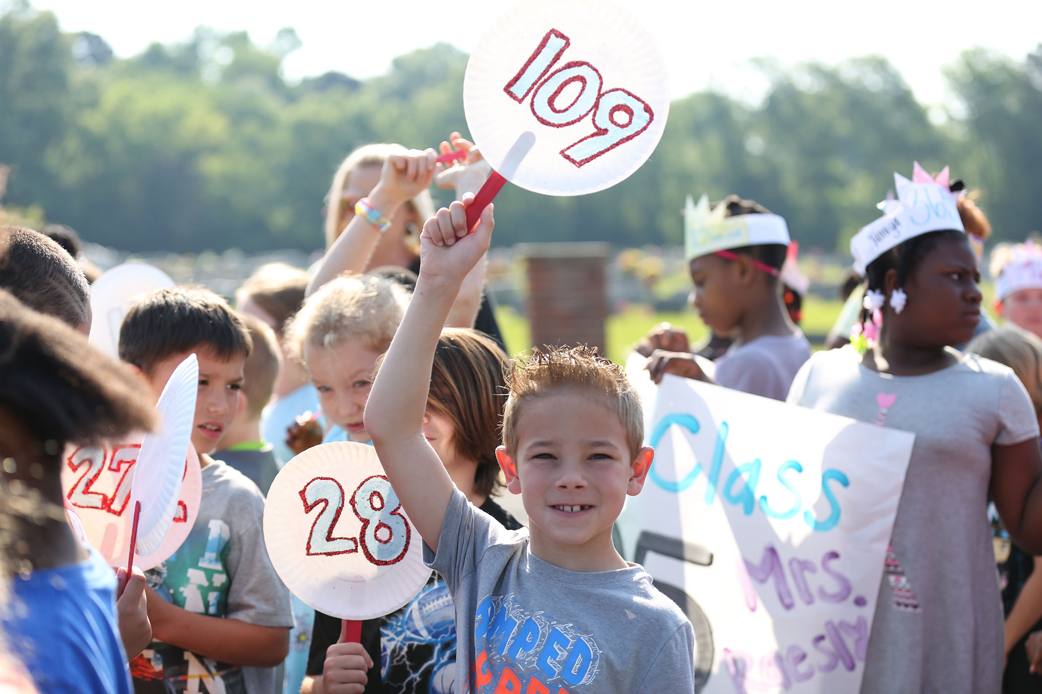 Student holds up a sign announcing that he read 109 books this year.