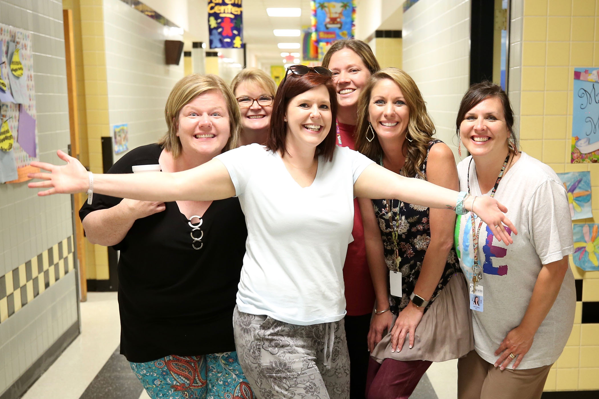 QLE teachers pose in the hallway.