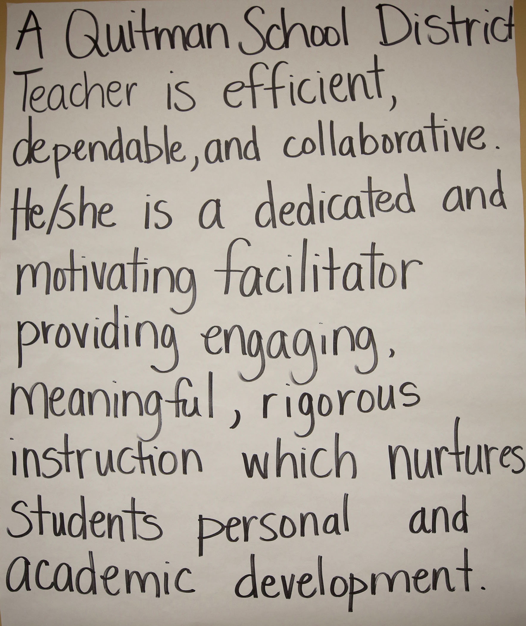 A poster of the definition of a teacher hangs on the wall in the board room.