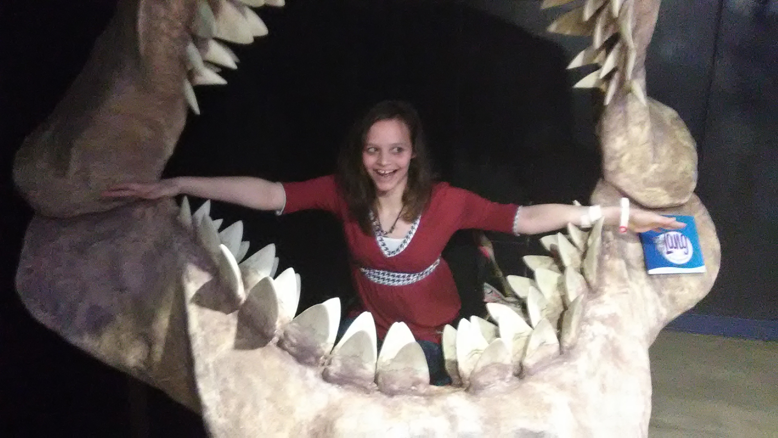 Chloe poses in the mouth of a dinosaur fossil, or replica.