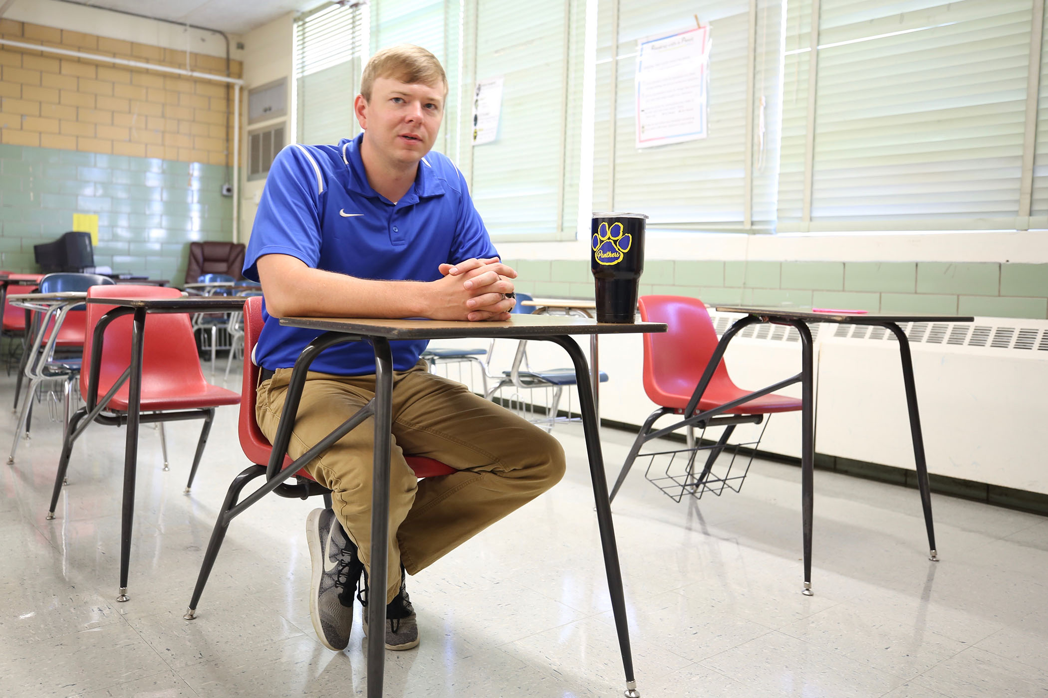 QJH teacher Scott Benson sits at one of his classroom's desk.