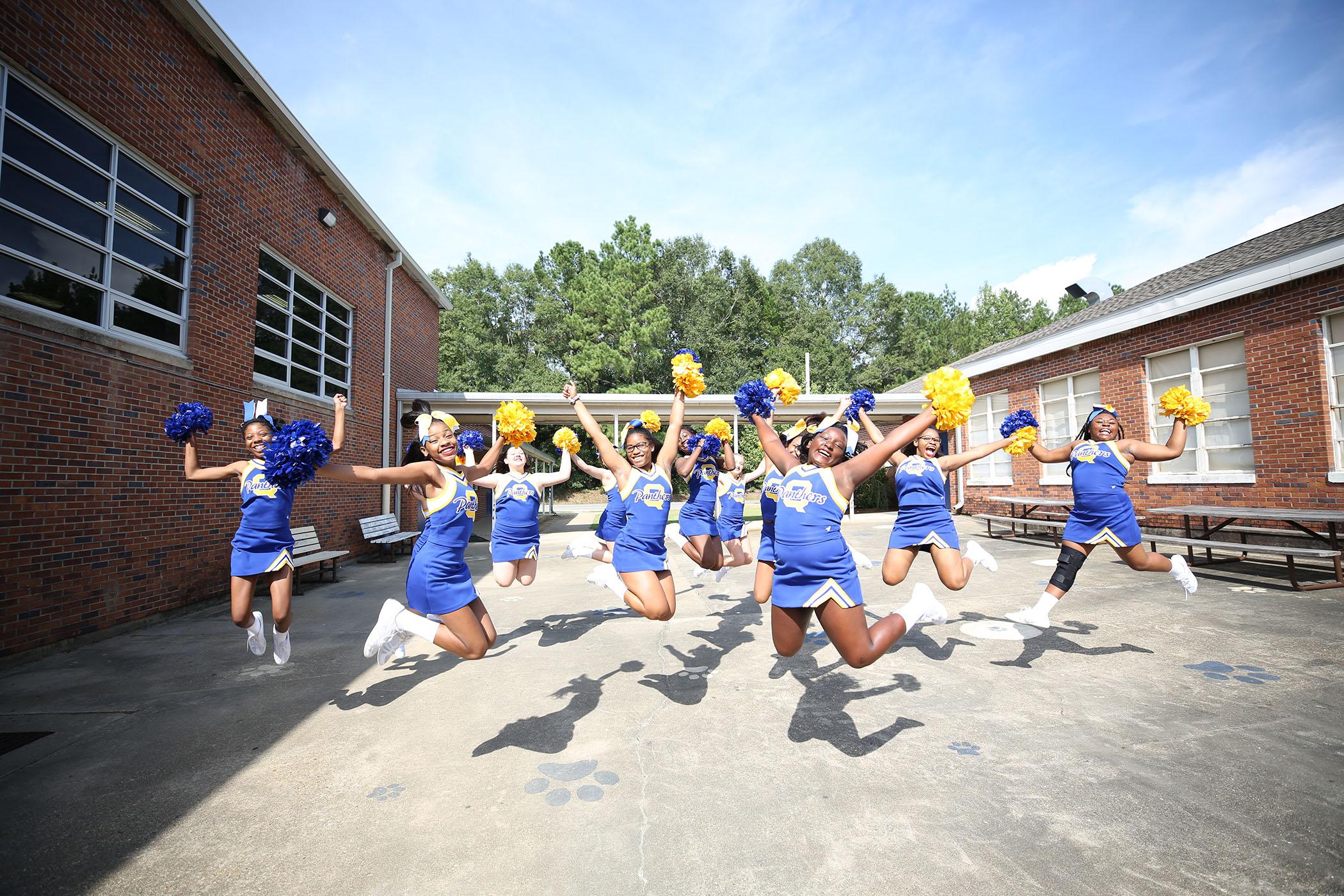 QJH cheerleaders do a simultaneous jump.