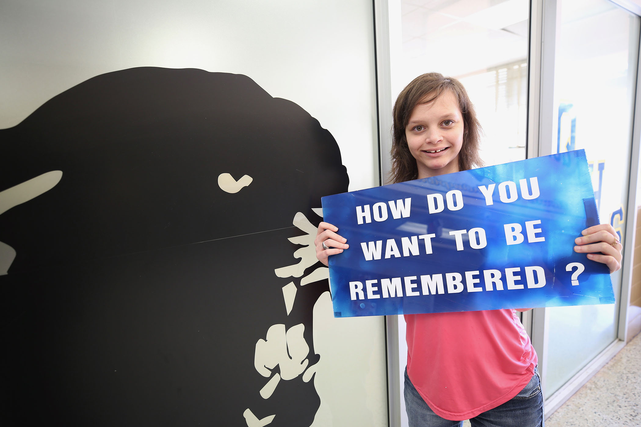 "Chloe poses with the ""HOW DO YOU WANT TO BE REMEMBERED?"" sign."