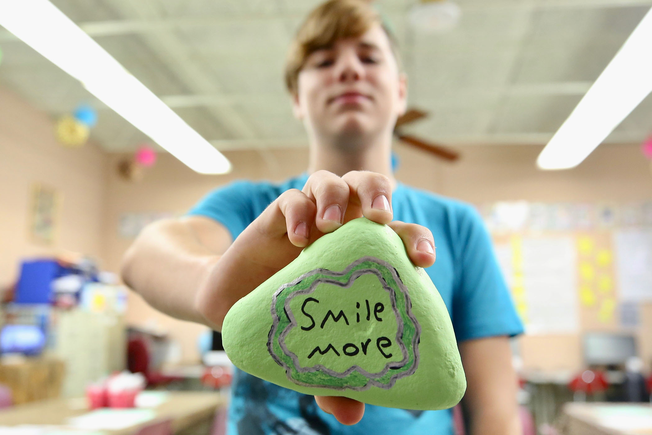 "A sixth grader holds a rock he painted. On it is written, ""Smile more."""