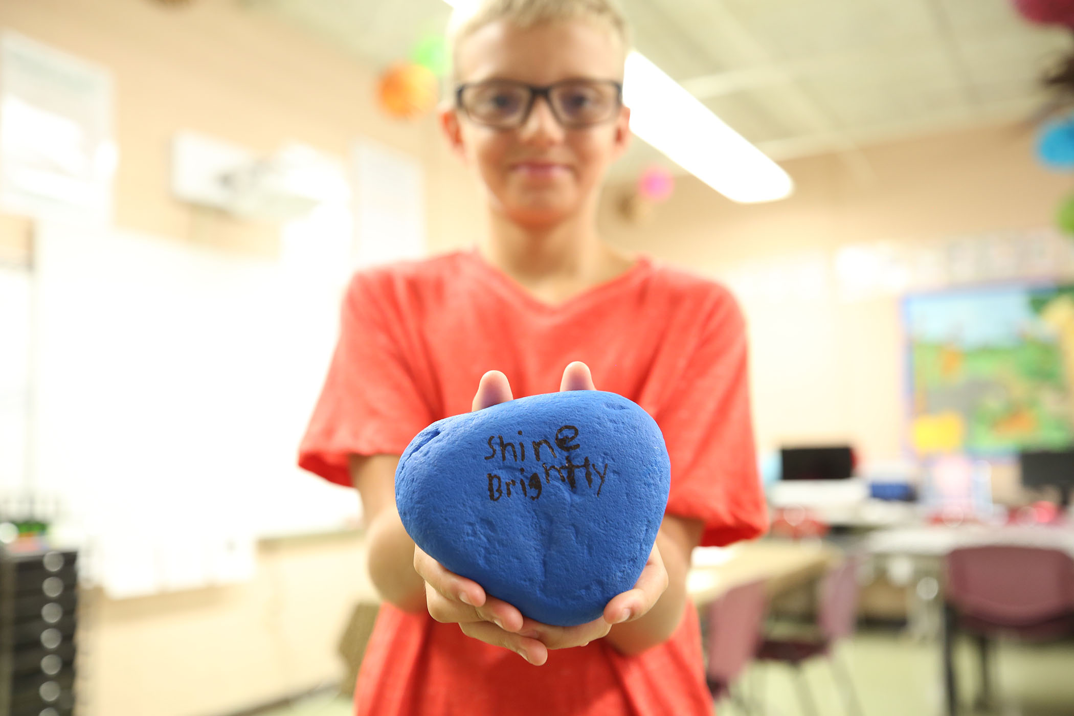 "A sixth grader holds a rock he painted. On it is written, ""Shine bright."""