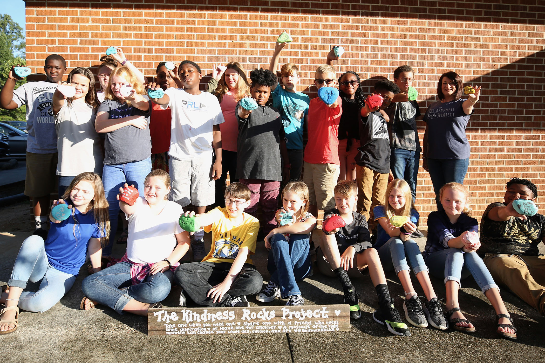 Sixth graders stand with their Kindness Rocks Project.
