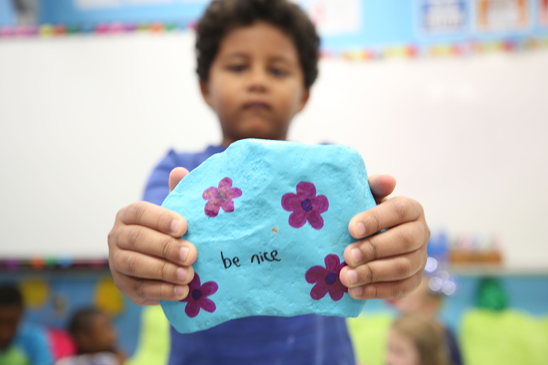 "A second grader holds a rock he painted. On it is written, ""Be nice."""