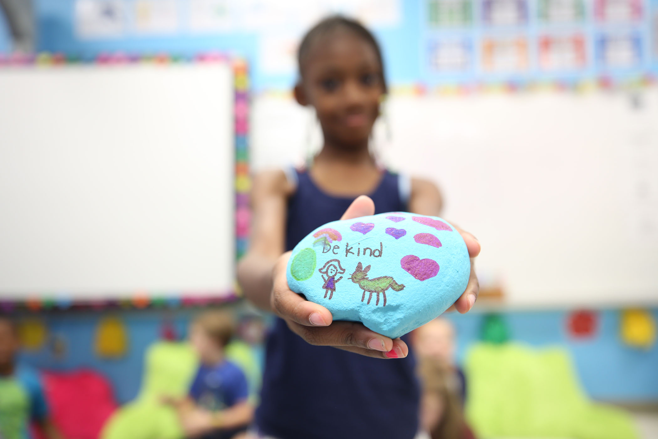 "A second grader holds a rock he painted. On it is written, ""Be kind."""