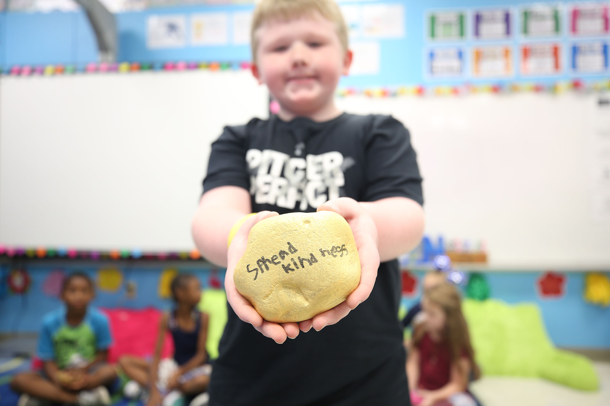"A second grader holds a rock he painted. On it is written, ""Spread kindness."""