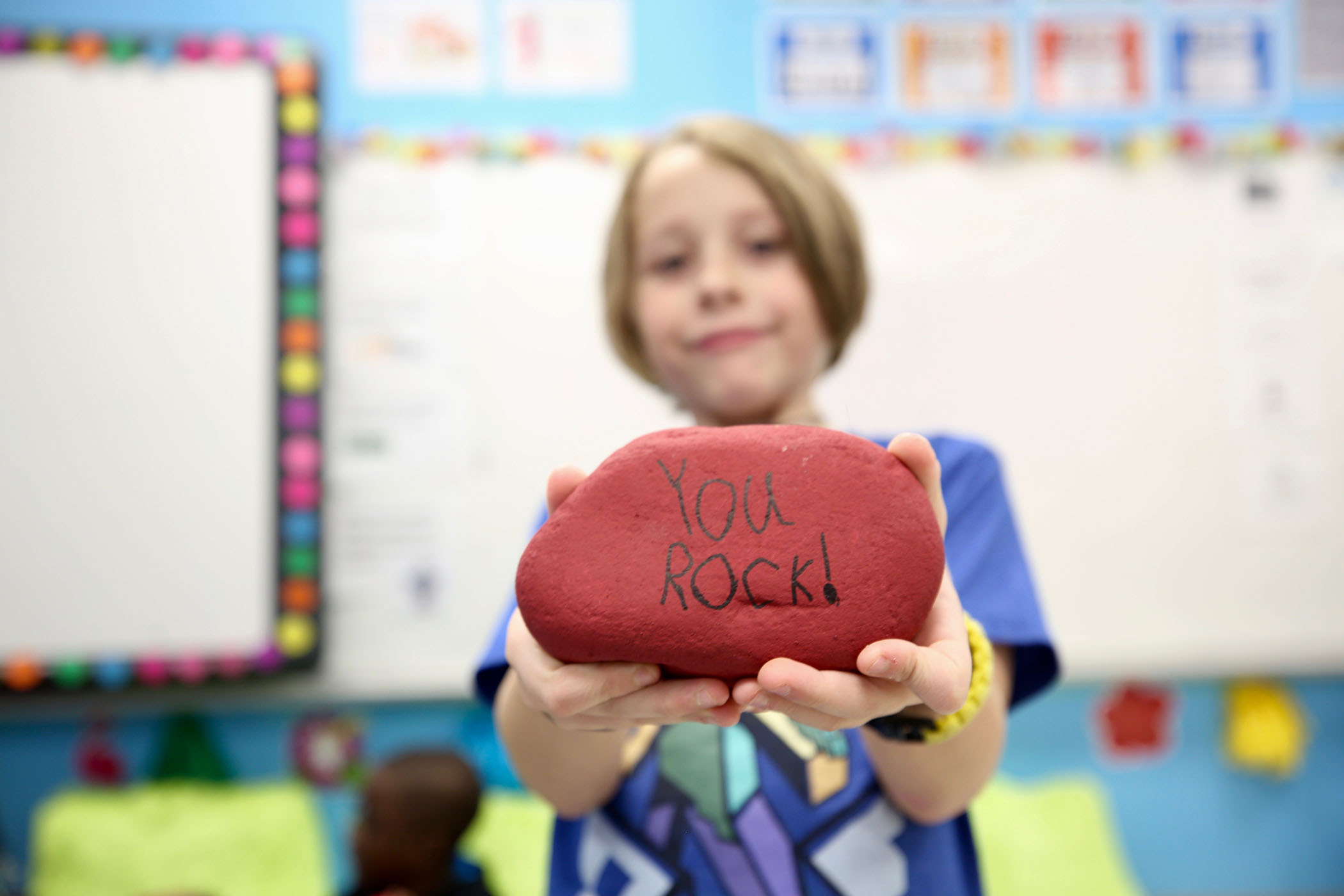 "A second grader holds a rock he painted. On it is written, ""You rock."""