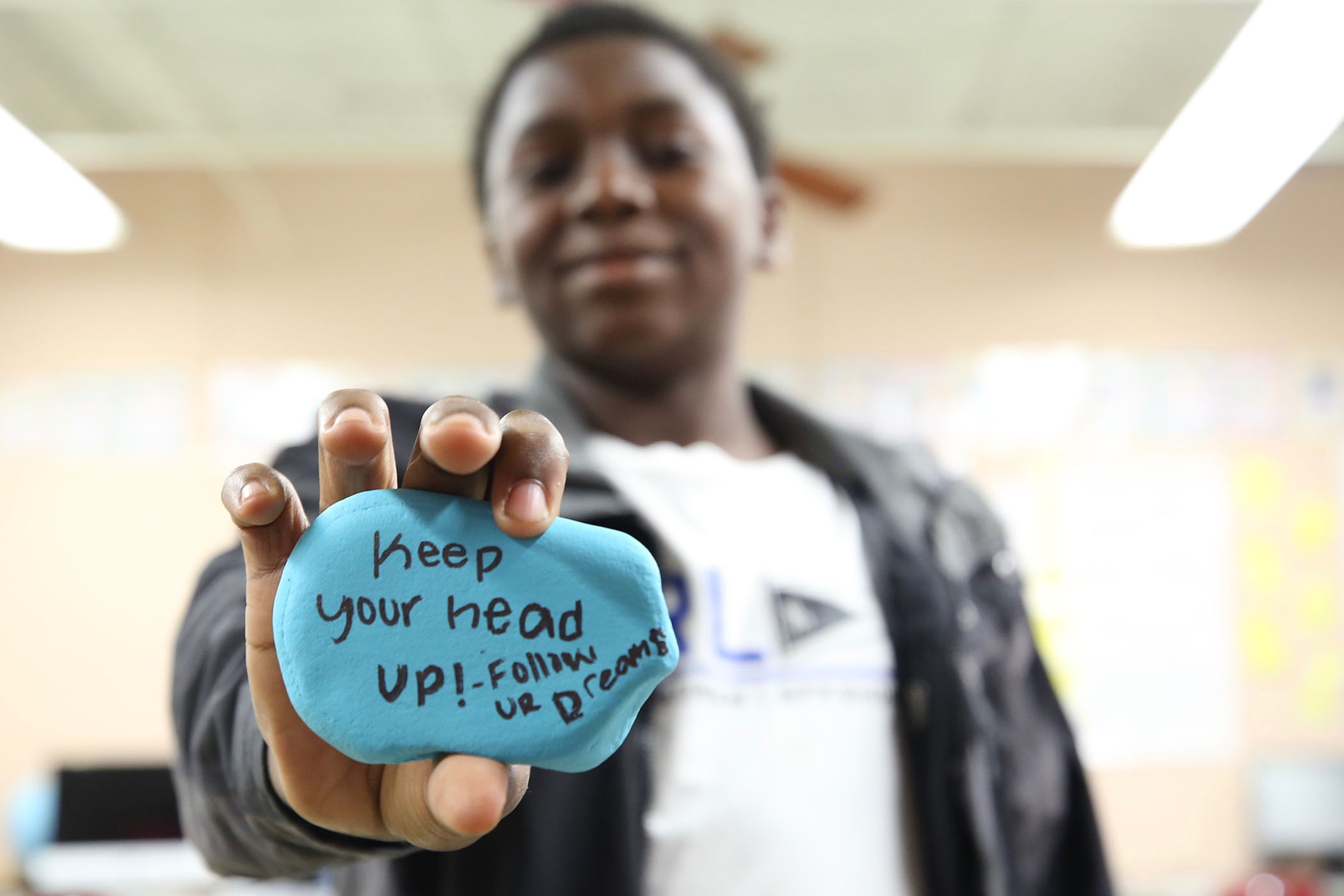 "A second grader holds a rock he painted. On it is written, ""Keep your head up. Follow your dreams."""