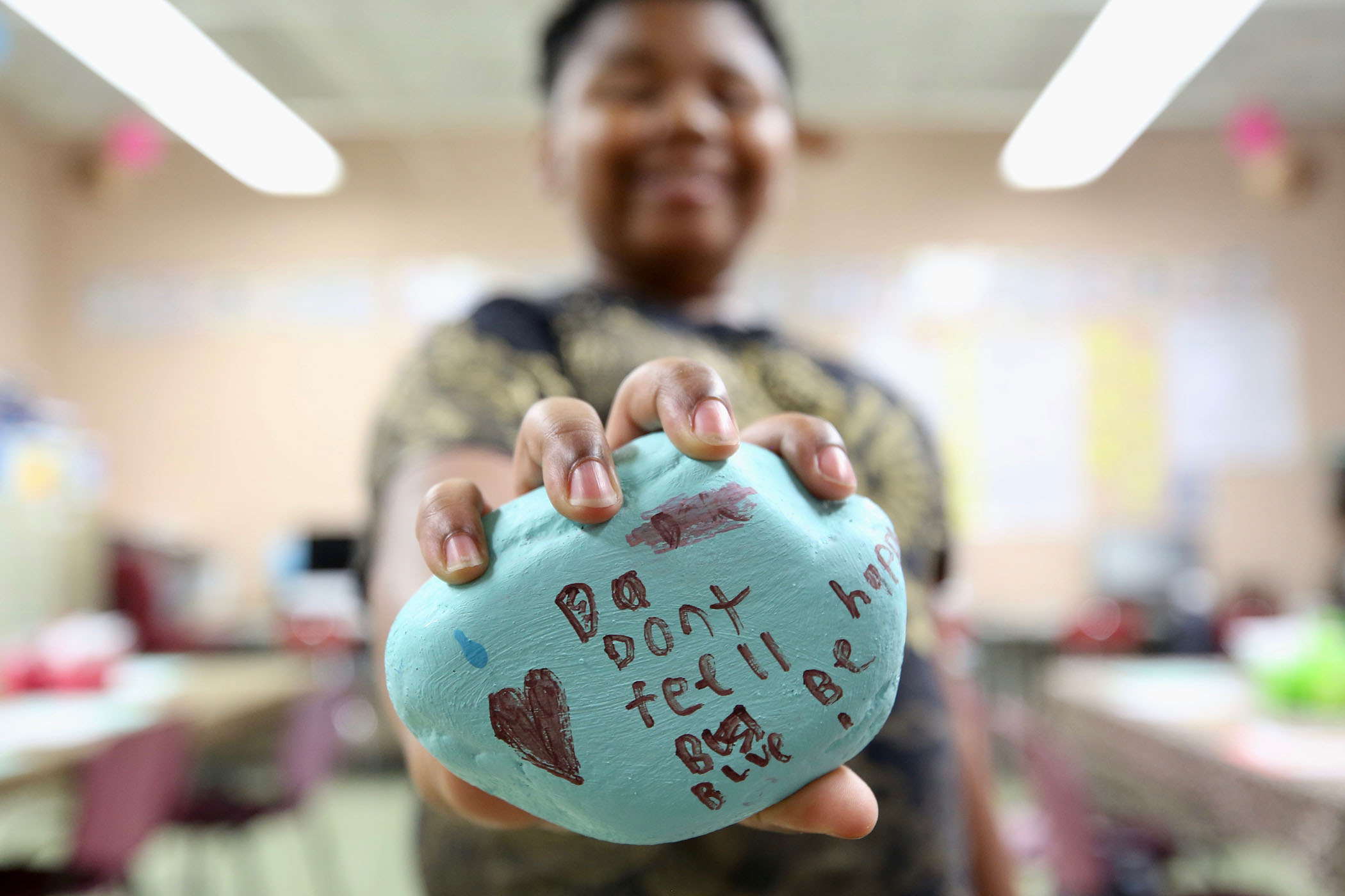 "A sixth grader holds a rock he painted. On it is written, ""Don't feel blue."""