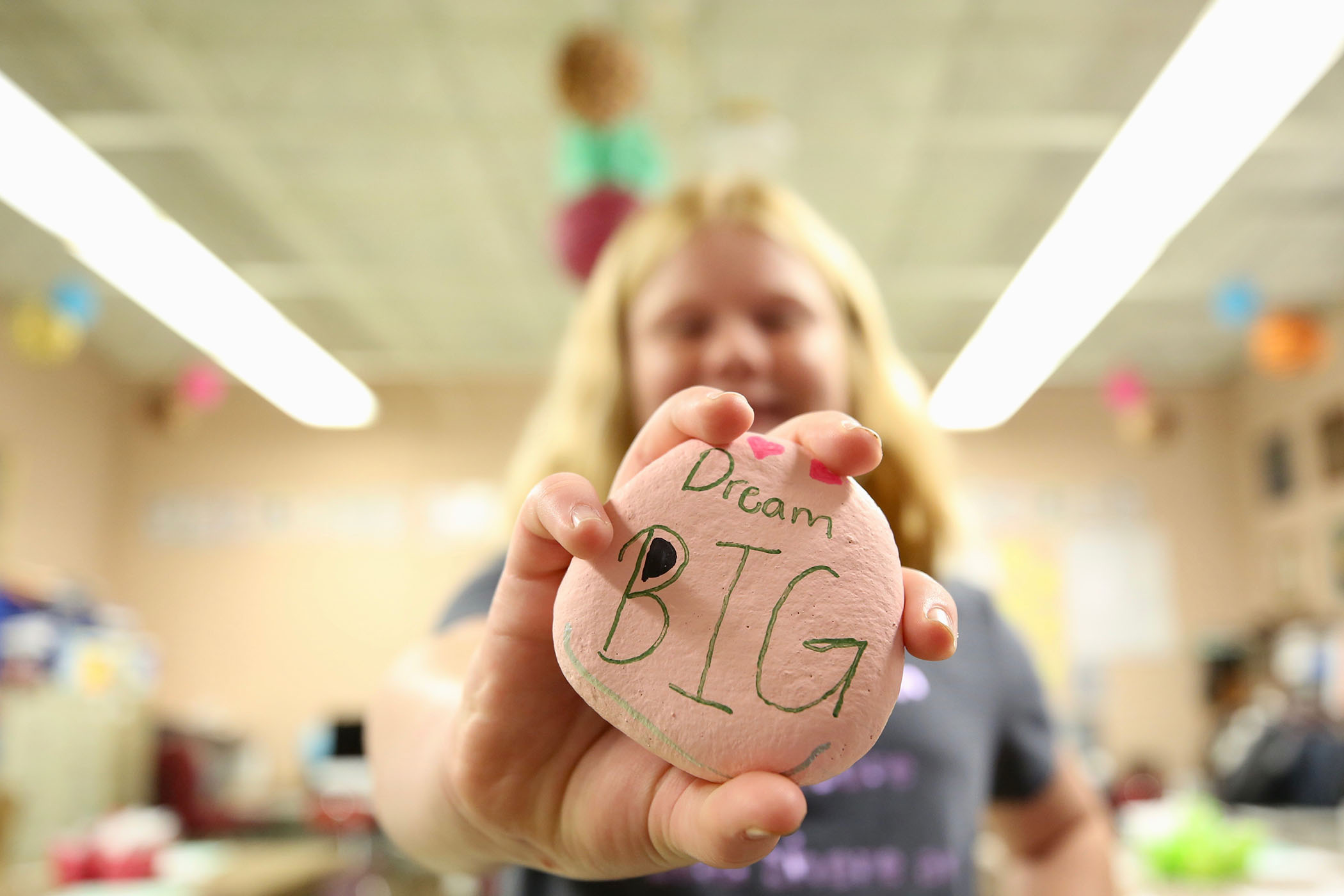 "A sixth grader holds a rock he painted. On it is written, ""Dream big."""